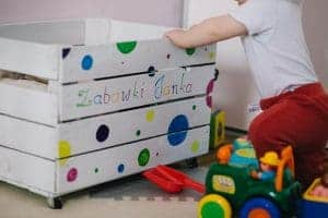 child with toys and toy box