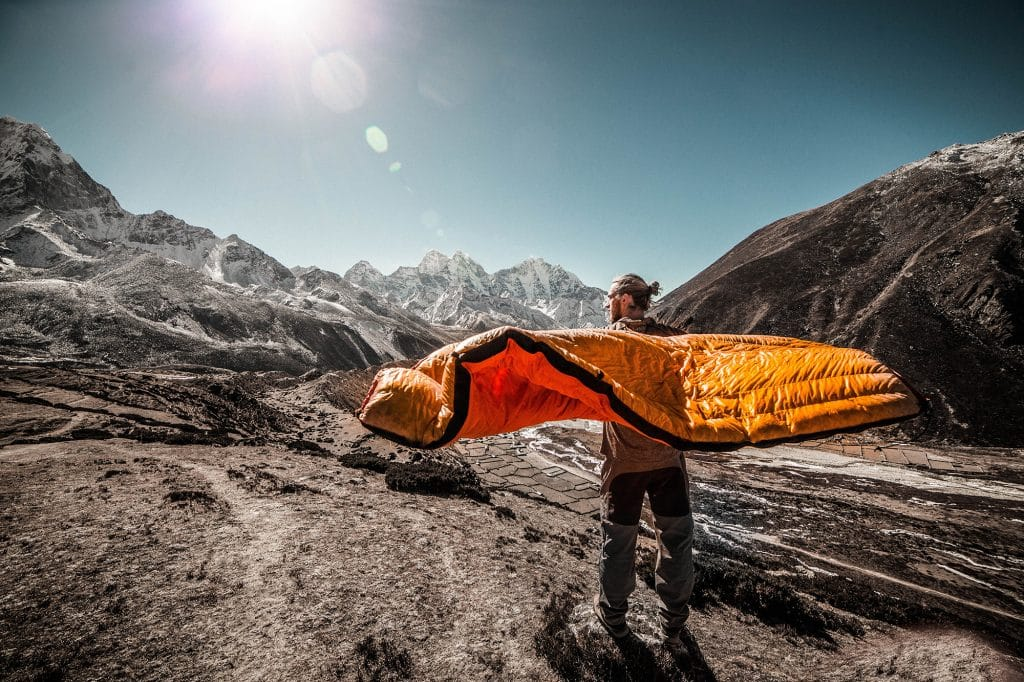 man carrying sleeping bag in the moutain
