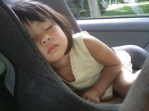 little girl sleeping inside the car