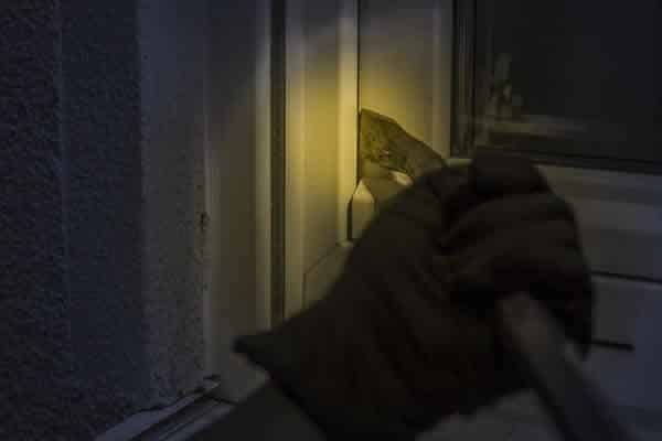 Burglar trying to open window at night using crowbar