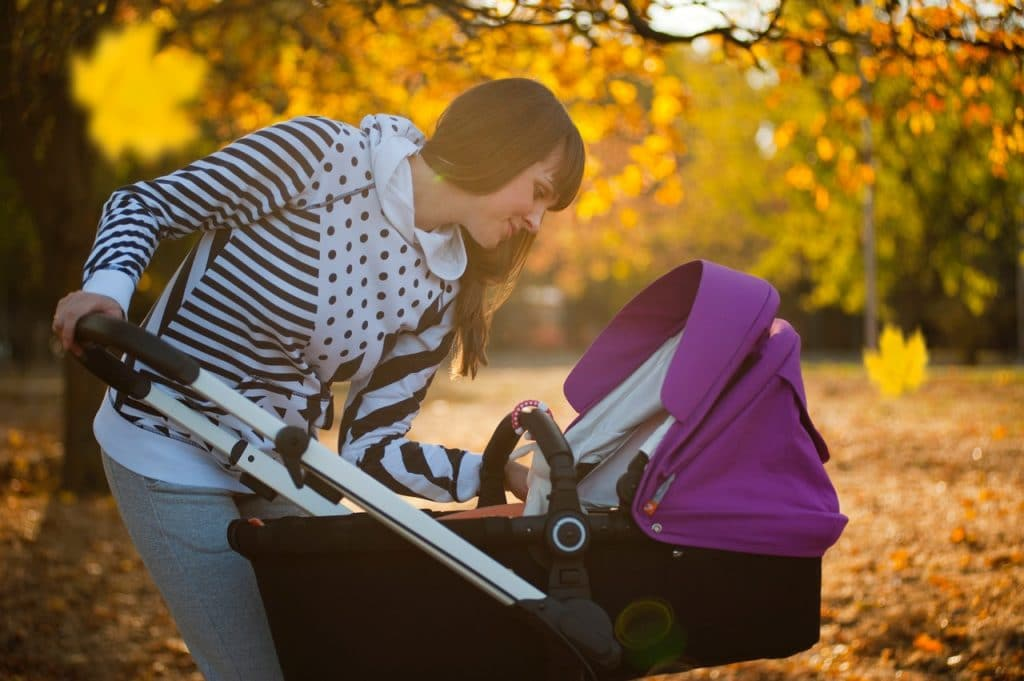 A woman looking her baby in the stroller