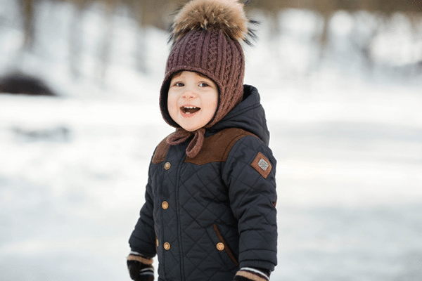 charming little boy funny winter hat poses