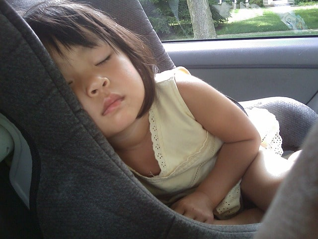 a little girl resting on her car seat