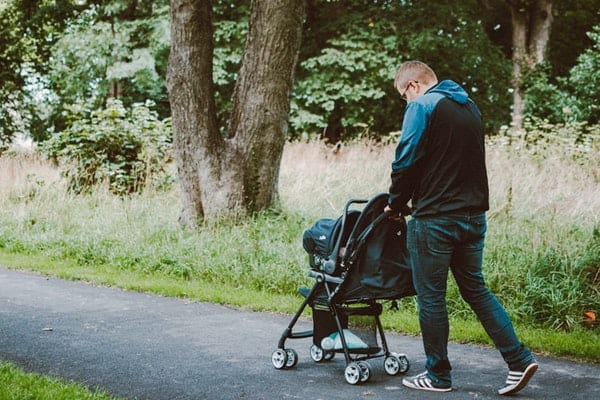 man pushing baby on stroller on permeable pavement