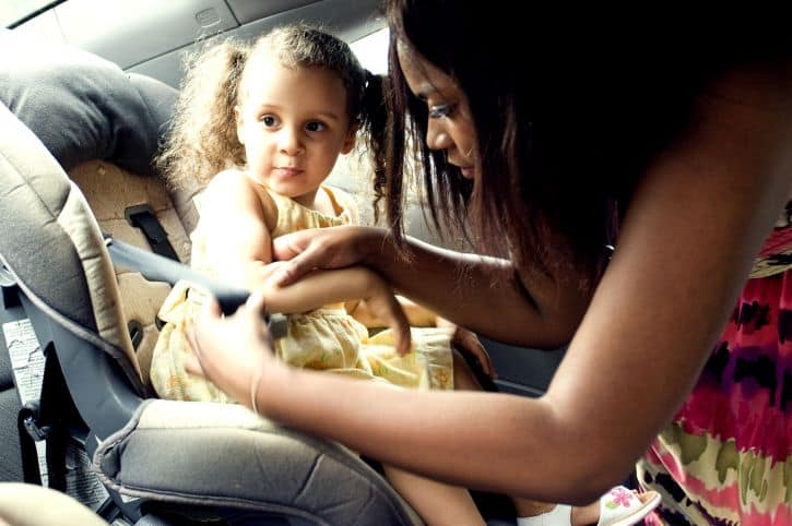 A mom buckles her child into a car seat