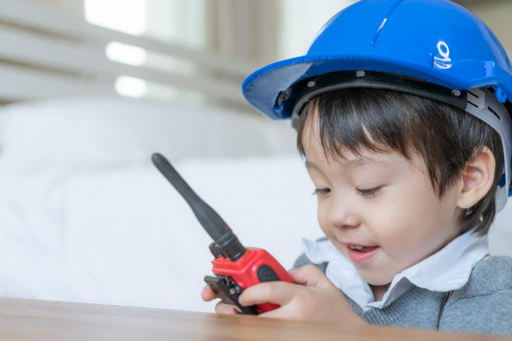 Little cute boy wearing blue helmet and enjoying to talking with red walkie-talkie redio in the bedroom