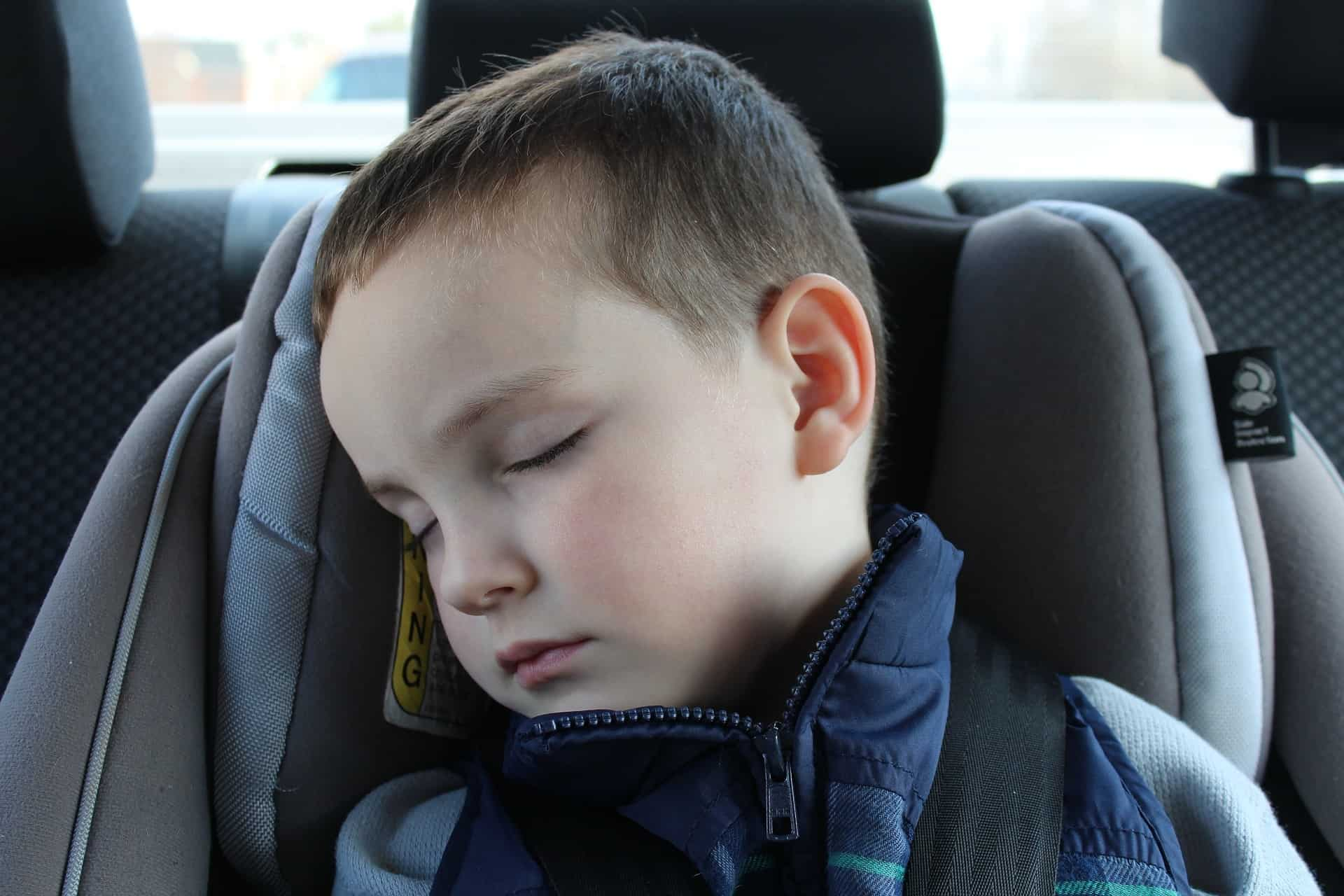 A boy sleeps in a Britax car seat