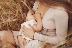 Mother with cute daughter. Mom breastfeeding her little daughter