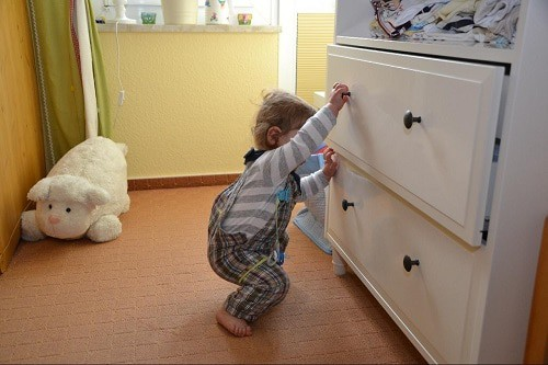 baby wearing jumper tried to open drawer