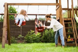 children on the swing. girls sisters swinging on a swing in the