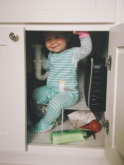 baby smiling inside cabinet