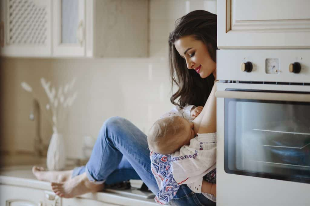 mother is breastfeeding in the kitchen