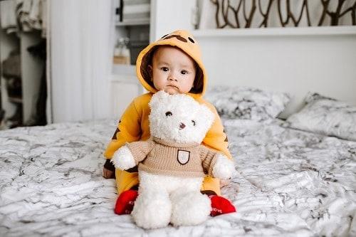 toddler sitting on bed beside white bear