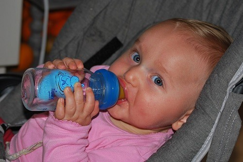baby drinking water on bottle formula