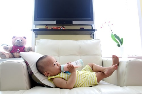 baby drinking milk in couch