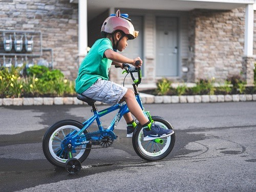 boy practicing bike with training wheels