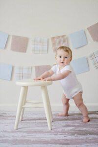 baby standing beside stool