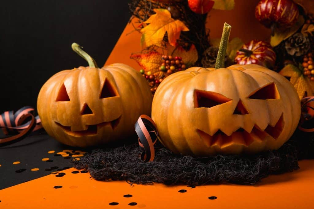 carved jack o lanterns sitting on an orange table cloth as Halloween Classroom Decorations
