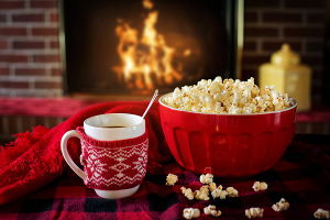 bowl of popcorn and a mug of hot chocolate in a knit cozy in front of a fireplace