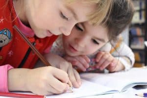 TWo young girls relieve their cabin fever with a workbook