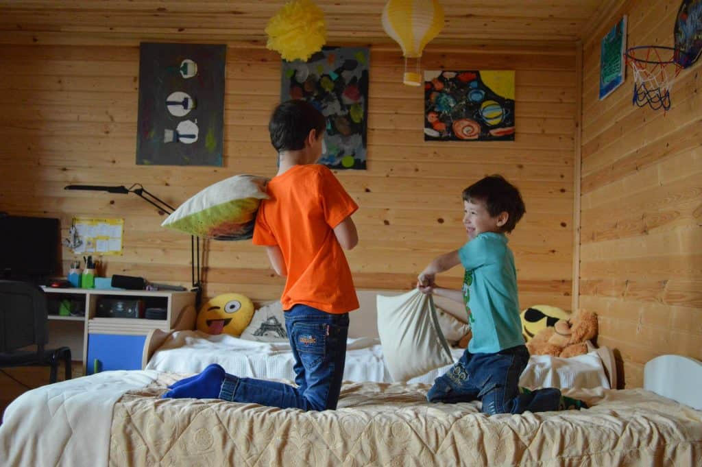 Two boys with cabin fever have a pillow fight on their bed