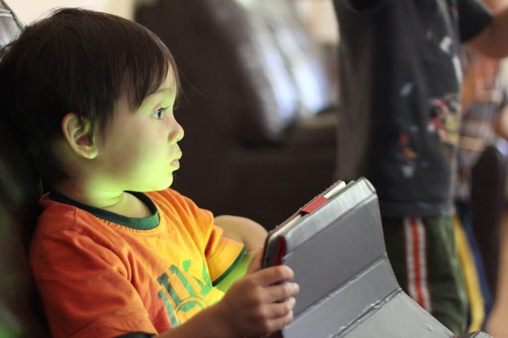 A young boy holding a tablet in his hands