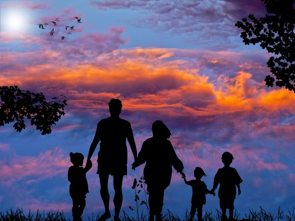 Two parents and three children enjoying their family travel packages at sunset